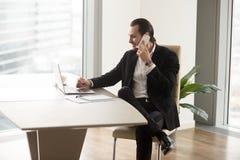 Προϊστάμενος της επιχείρησης στην αφή με τους συνεργάτες τηλεφωνικώς Στοκ Εικόνα