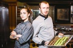 Προϊόντα βιομηχανιών ζαχαρωδών προϊόντων προετοιμασιών επαγγέλματος Καυκάσιοι άνδρας και γυναίκα δύο αρχιμάγειρας ζύμης ομαδικής  στοκ φωτογραφία
