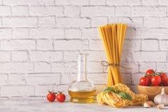 Προϊόντα για το μαγείρεμα - ζυμαρικά, ντομάτες, σκόρδο, ελαιόλαδο, βασιλικός Στοκ Εικόνες