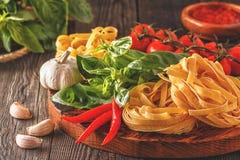 Προϊόντα για το μαγείρεμα - ζυμαρικά, ντομάτες, σκόρδο, πιπέρι, και basi Στοκ φωτογραφία με δικαίωμα ελεύθερης χρήσης
