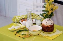 Προϊόντα κέικ Πάσχας στον πράσινο πίνακα με τα λουλούδια στοκ εικόνες