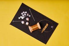 Προϊόντα και εργαλεία κεντητικής Νήματα μετάλλων σπειρών, μαργαριτάρια και μια καρφίτσα με τη βελόνα στο Μαύρο αισθητό στοκ εικόνες