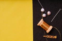 Προϊόντα και εργαλεία κεντητικής Νήματα μετάλλων σπειρών, μαργαριτάρια και μια καρφίτσα με τη βελόνα στο Μαύρο αισθητό στοκ φωτογραφία με δικαίωμα ελεύθερης χρήσης