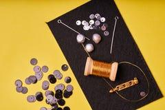 Προϊόντα και εργαλεία κεντητικής Νήματα μετάλλων σπειρών, μαργαριτάρια και μια καρφίτσα με τη βελόνα στο Μαύρο αισθητό στοκ εικόνα