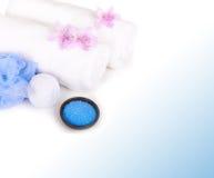 Άσπρες πετσέτες, άλας, σφουγγάρι λουτρών και αρωματικά λουλούδια Στοκ Εικόνα