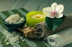 Προϊόντα SPA στο ξύλινο λουλούδι ορχιδεών υποβάθρου, κύπελλο με τη θάλασσα Στοκ φωτογραφία με δικαίωμα ελεύθερης χρήσης
