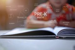 Προ παιδικών σταθμών κείμενα καταλόγων Math υπαγόμενα με το υπόβαθρο παιδιών, καθόταν και διάβαζε ένα βιβλίο σε έναν άσπρο πίνακα στοκ εικόνες με δικαίωμα ελεύθερης χρήσης