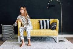 Προ παιδί εφήβων στον καναπέ ενάντια στο μαύρο τοίχο στη σύγχρονη διαβίωση Στοκ φωτογραφία με δικαίωμα ελεύθερης χρήσης