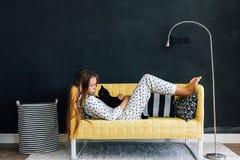 Προ παιδί εφήβων στον καναπέ ενάντια στο μαύρο τοίχο στη σύγχρονη διαβίωση Στοκ Εικόνες