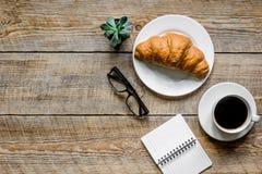Πρωί επιχειρηματιών με τα γυαλιά, φλιτζάνι του καφέ και croissant στο ξύλινο πρότυπο άποψης επιτραπέζιου υποβάθρου τοπ Στοκ Εικόνες