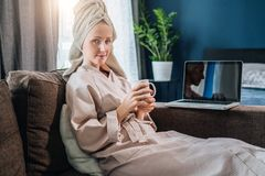 Πρωί Νέα γυναίκα στο μπουρνούζι και πετσέτα στην επικεφαλής συνεδρίαση στο δωμάτιο στον καναπέ, καφές κατανάλωσης, που λειτουργεί στοκ εικόνα