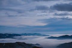 Πρωί χειμερινών Χριστουγέννων της Misty πέρα από την κορυφή βουνών στοκ φωτογραφία