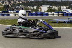 Πρωτάθλημα Karting Ο οδηγός στα karts που φορούν το κράνος, συναγωνιμένος το κοστούμι συμμετέχει στη φυλή kart Το Karting παρουσι Στοκ φωτογραφία με δικαίωμα ελεύθερης χρήσης