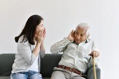 Πρόβλημα απώλειας ακοής, ασιατικός ηληκιωμένος με το χέρι στη χειρονομία αυτιών που προσπαθεί να ακούσει φωνάζοντας γυναίκα στοκ φωτογραφίες