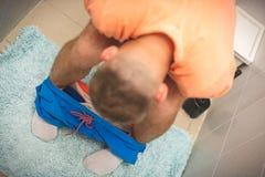 Πρόβλημα που πηγαίνει στην τουαλέτα Άποψη κινηματογραφήσεων σε πρώτο πλάνο της αρσενικής συνεδρίασης στο κάθισμα τουαλετών στοκ φωτογραφία
