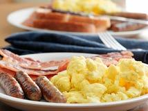 Πρόγευμα - ανακατωμένα αυγά, λουκάνικο, και μπέϊκον Στοκ Φωτογραφίες