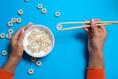 Πρόγευμα δημητριακών με το γάλα και chopsticks για τα σούσια στο μπλε υπόβαθρο στοκ φωτογραφίες