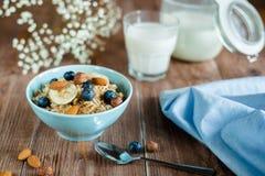 Πρόγευμα κουάκερ γάλακτος με τα καρύδια και τα μούρα Στοκ Φωτογραφία