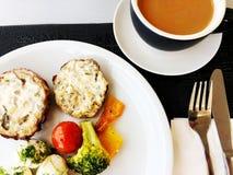 Πρόγευμα με τα μανιτάρια και τις ντομάτες και μπρόκολο, καφές σε ένα άσπρο πιάτο στον πίνακα Κλείστε αυξημένος Στοκ Εικόνα