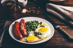 Πρόγευμα με τα τηγανισμένα αυγά, τα λουκάνικα και τα πράσινα μπιζέλια στοκ εικόνα με δικαίωμα ελεύθερης χρήσης