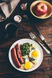 Πρόγευμα με τα τηγανισμένα αυγά, τα λουκάνικα και τα πράσινα μπιζέλια στοκ εικόνες