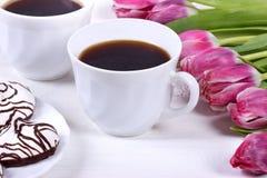 Πρόγευμα με τον καφέ, τις φρέσκα τουλίπες και το κέικ στον ξύλινο πίνακα Στοκ εικόνες με δικαίωμα ελεύθερης χρήσης