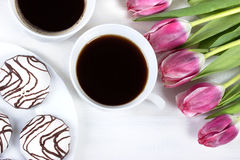 Πρόγευμα με τον καφέ, τις φρέσκα τουλίπες και το κέικ στον ξύλινο πίνακα Στοκ φωτογραφία με δικαίωμα ελεύθερης χρήσης