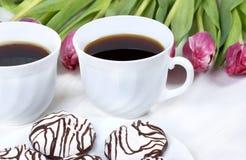 Πρόγευμα με τον καφέ, τις φρέσκα τουλίπες και το κέικ στον ξύλινο πίνακα Στοκ Εικόνες