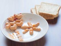 Πρόγευμα με το λουκάνικο ψωμιού και καρδιών στον πίνακα Στοκ Εικόνες