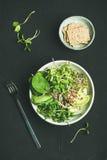 Πρόγευμα με το σπανάκι, το arugula, το αβοκάντο, τους σπόρους και τους νεαρούς βλαστούς, τοπ άποψη Στοκ Φωτογραφία