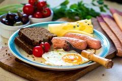Πρόγευμα με το τηγανισμένο αυγό, λουκάνικα, ψωμί, ντομάτα, τυρί Στοκ Εικόνα