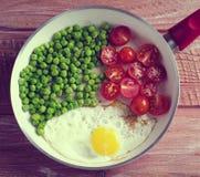 Πρόγευμα με το τηγανισμένο αυγό, τα πράσινα μπιζέλια και τις ντομάτες κερασιών Στοκ εικόνα με δικαίωμα ελεύθερης χρήσης
