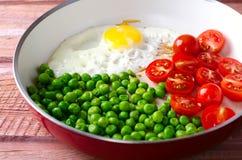 Πρόγευμα με το τηγανισμένο αυγό, τα πράσινα μπιζέλια και τις ντομάτες κερασιών Στοκ Εικόνα