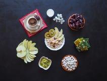 Πρόγευμα με το muesli στο μαύρο υπόβαθρο Μαύρος καφές με τα τουρκικό γλυκά, το muesli, τις ημερομηνίες και το γάλα Γλυκά τρόφιμα  Στοκ Φωτογραφίες