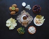 Πρόγευμα με το muesli στο μαύρο υπόβαθρο Μαύρος καφές με τα τουρκικό γλυκά, το muesli, τις ημερομηνίες και το γάλα Γλυκά τρόφιμα  Στοκ εικόνα με δικαίωμα ελεύθερης χρήσης