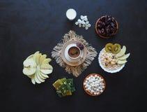 Πρόγευμα με το muesli στο μαύρο υπόβαθρο Μαύρος καφές με τα τουρκικό γλυκά, το muesli, τις ημερομηνίες και το γάλα Γλυκά τρόφιμα  Στοκ Φωτογραφία