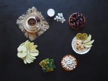 Πρόγευμα με το muesli στο μαύρο υπόβαθρο Μαύρος καφές με τα τουρκικό γλυκά, το muesli, τις ημερομηνίες και το γάλα Γλυκά τρόφιμα  Στοκ Εικόνες
