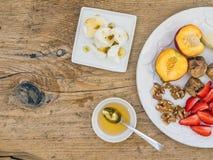 Πρόγευμα που τίθεται με τη φρέσκια φράουλα, μπανάνα, ροδάκινο, ξηρά σύκα, wa Στοκ Εικόνες