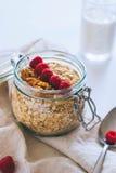 Πρόγευμα πρωινού, oatmeal με τα κόκκινα σμέουρα και τα ξύλα καρυδιάς Στοκ Φωτογραφία