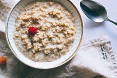 Πρόγευμα πρωινού, oatmeal στο γάλα με τα σμέουρα Στοκ φωτογραφία με δικαίωμα ελεύθερης χρήσης