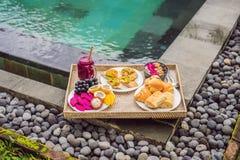 Πρόγευμα σε έναν δίσκο με τα φρούτα, κουλούρια, σάντουιτς αβοκάντο, κύπελλο καταφερτζήδων από τη λίμνη Θερινή υγιεινή διατροφή, v στοκ εικόνες με δικαίωμα ελεύθερης χρήσης