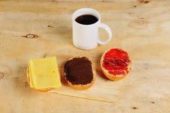 Πρόγευμα σε έναν πάγκο με τους ρόλους ψωμιού και ένα φλιτζάνι του καφέ Στοκ Εικόνες