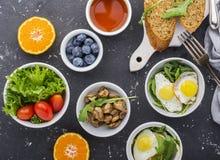 Πρόγευμα σε ένα σκοτεινό υπόβαθρο: τηγανισμένα αυγά ορτυκιών, arugula, φρέσκο ψωμί, μαρούλι, ντομάτες, πορτοκάλια, καρύδια, τσάι, Στοκ Εικόνες