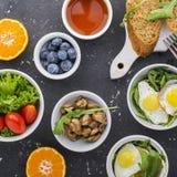 Πρόγευμα σε ένα σκοτεινό υπόβαθρο: τηγανισμένα αυγά ορτυκιών, arugula, φρέσκο ψωμί, μαρούλι, ντομάτες, πορτοκάλια, καρύδια, τσάι, Στοκ φωτογραφία με δικαίωμα ελεύθερης χρήσης