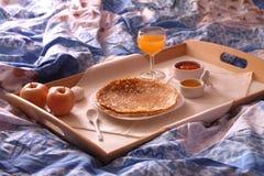 Πρόγευμα στο κρεβάτι με τις λεπτές τηγανίτες, τη σπιτική μαρμελάδα και το χυμό από πορτοκάλι Στοκ Φωτογραφία