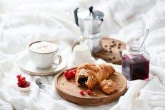 Πρόγευμα στο κρεβάτι με croissant, τον καφέ και τη μαρμελάδα Στοκ εικόνα με δικαίωμα ελεύθερης χρήσης
