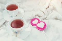 Πρόγευμα στο κρεβάτι στην ημέρα βαλεντίνων Φλυτζάνι του τσαγιού και των γλυκών καραμελών Έννοια αγάπης ή διακοπών Στοκ Εικόνες