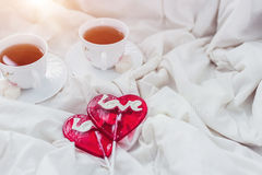 Πρόγευμα στο κρεβάτι στην ημέρα βαλεντίνων Φλυτζάνι του τσαγιού και των γλυκών καραμελών Έννοια αγάπης ή διακοπών Στοκ εικόνα με δικαίωμα ελεύθερης χρήσης