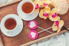 Πρόγευμα στο κρεβάτι στην ημέρα βαλεντίνων Φλυτζάνι του τσαγιού και των γλυκών καραμελών Έννοια αγάπης ή διακοπών Στοκ εικόνες με δικαίωμα ελεύθερης χρήσης