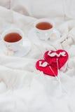 Πρόγευμα στο κρεβάτι στην ημέρα βαλεντίνων Φλυτζάνι του τσαγιού και των γλυκών καραμελών Έννοια αγάπης ή διακοπών Στοκ φωτογραφία με δικαίωμα ελεύθερης χρήσης